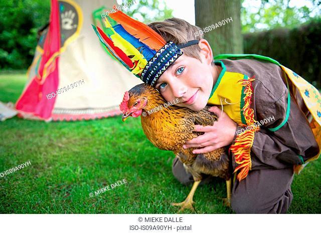 Boy dressed in Native American costume holding chicken, portrait