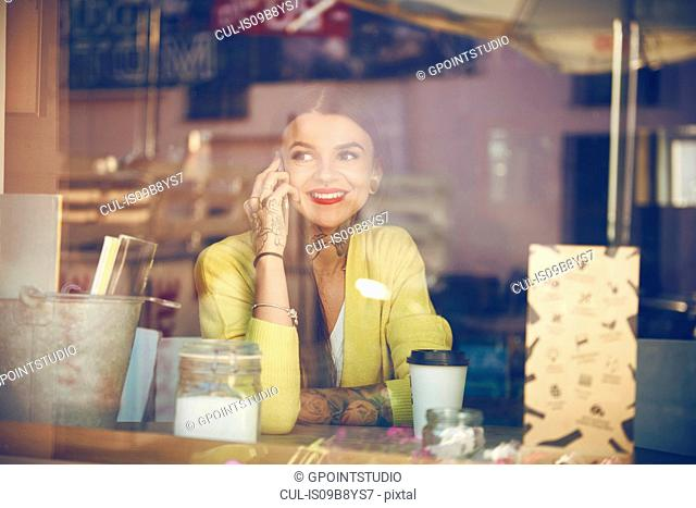 Young woman sitting in cafe, using smartphone, tattoos on hand, view through cafe window