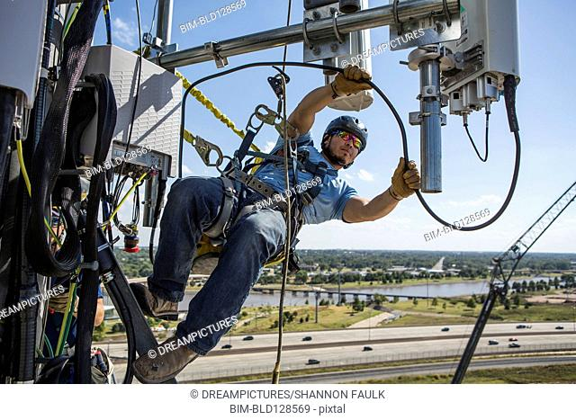 Hispanic worker harnessed to cell tower