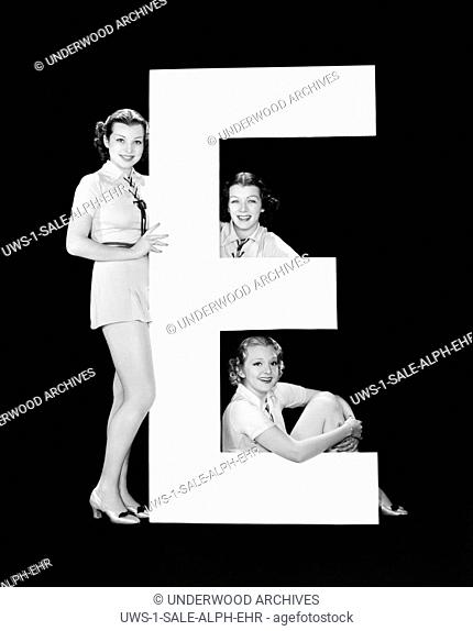 Hollywood, California: c. 1935.The letter E accompanied by three attractive young women