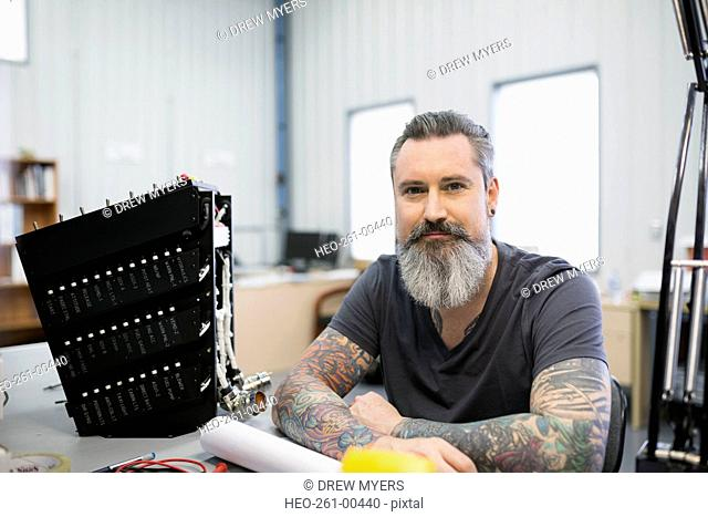 Portrait confident helicopter technician repairing module