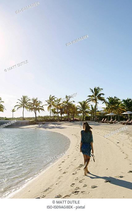 Young woman strolling on beach, Providenciales, Turks and Caicos Islands, Caribbean