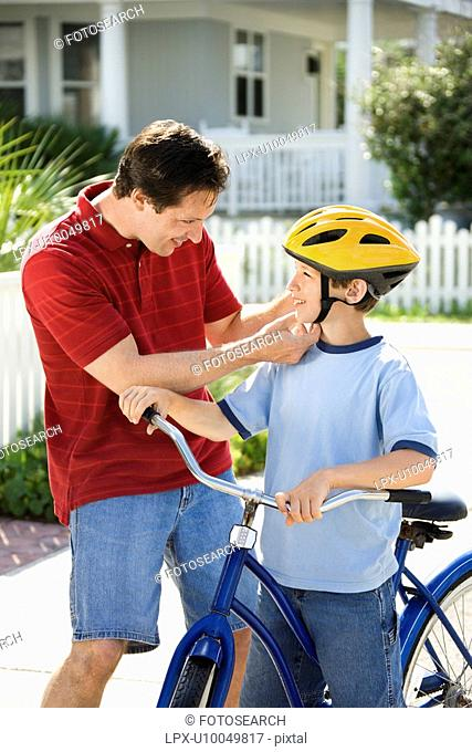 Caucasian mid-adult dad strapping bicycle helmet on pre-teen son