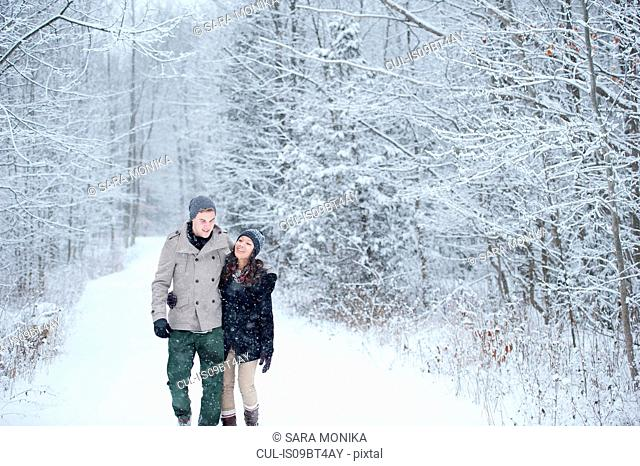 Romantic young couple strolling in snowy forest, Ontario, Canada