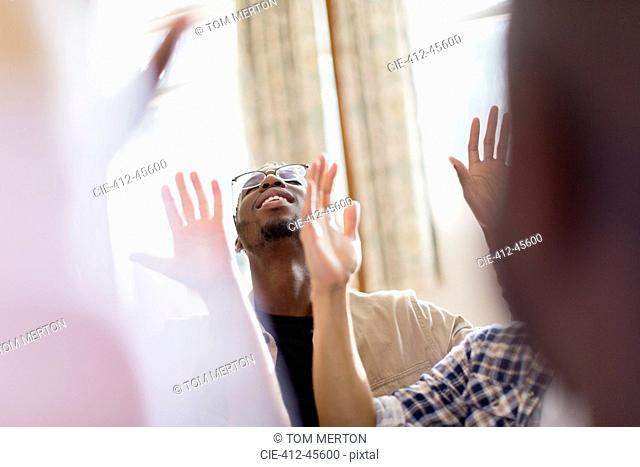 Smiling man with arms raised praying in prayer group
