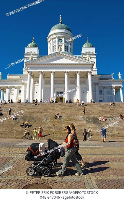 Women pushing prams past Tuomiokirkko cathedral at Senaatintori square in Helsinki Finland Europe