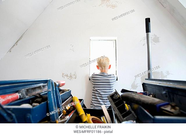 Boy looking out of window in attic to be renovated with toolbox in foreground