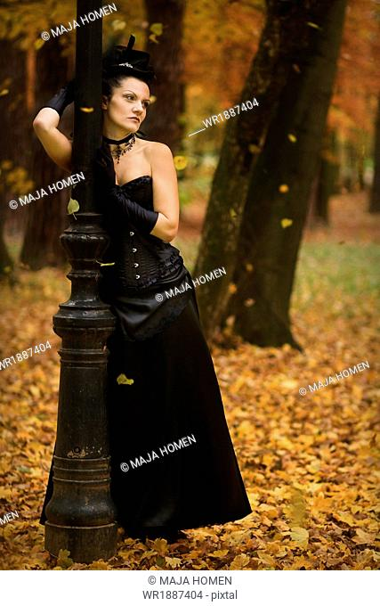 Young woman in Gothic style fashion leaning against lamp, Croatia, Europe