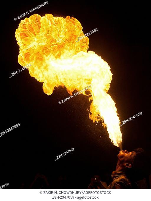 A boy fire splitting using kerosene oil during shakrain festival in Old Dhaka