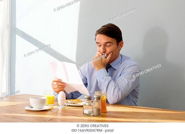 man at breakfast table reading a letter