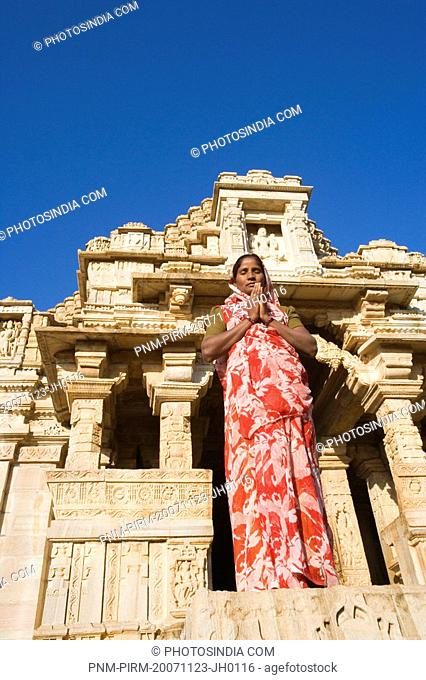 Woman standing in a prayer position in front of a temple, Kumbha Shyam Temple, Chittorgarh, Rajasthan, India