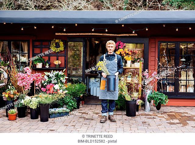 Caucasian florist holding flowers outside shop