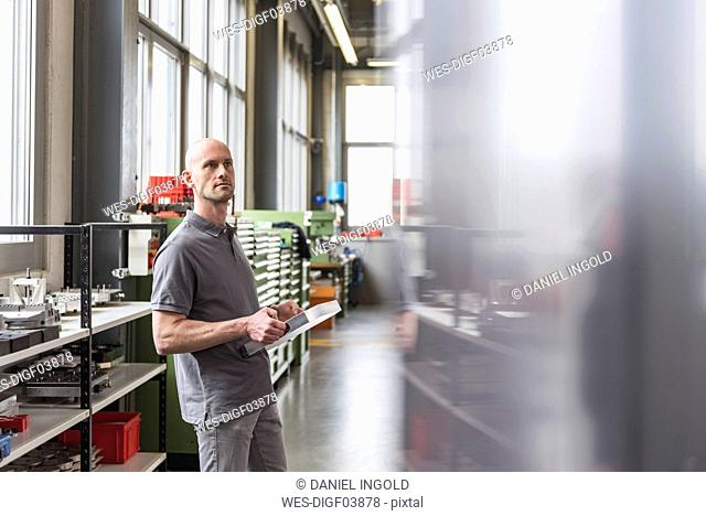 Man standing in modern factory holding product