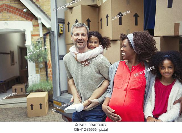 Portrait smiling pregnant multi-ethnic young family moving into new house