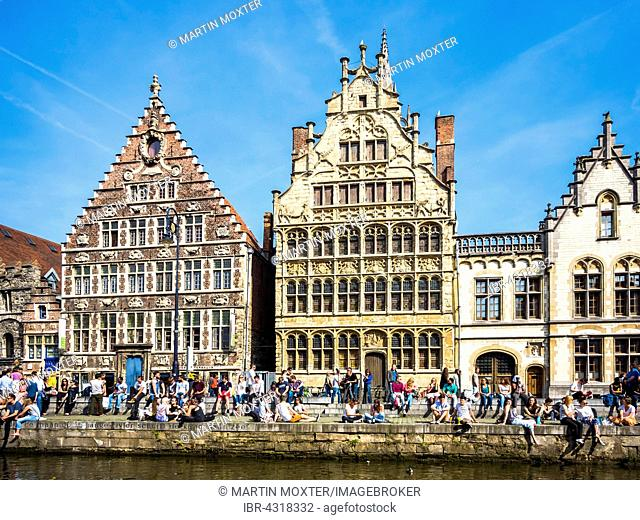 Leie River and promenade on the Graslei with old guild houses, young people on the shore, Ghent, Flanders, Belgium