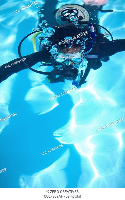 Young female scuba diver training in swimming pool