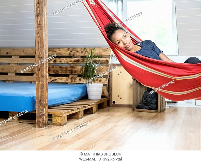 Smiling young woman lying in hammock