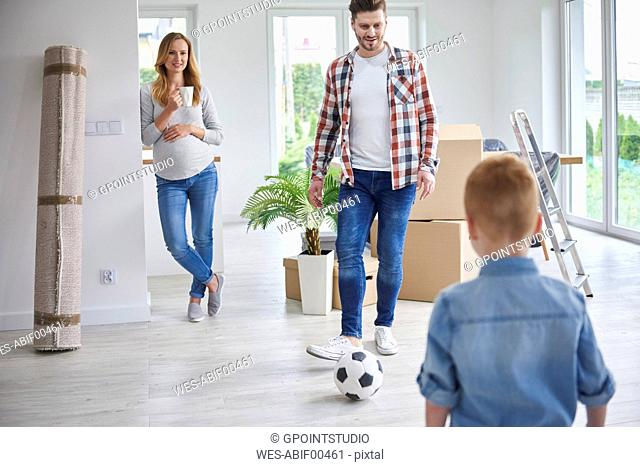 Family playing football in new flat