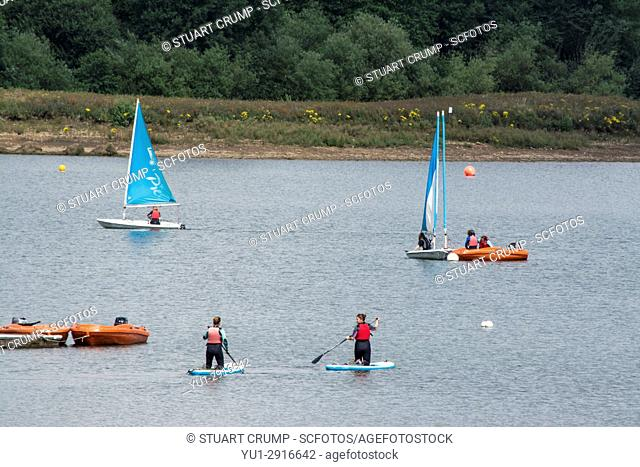 Sailing boats and paddle boards on the Resevoir at Casington Water in Derbyshire UK