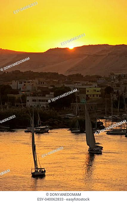 Felucca boats sailing on the Nile river at sunset, Aswan, Egypt