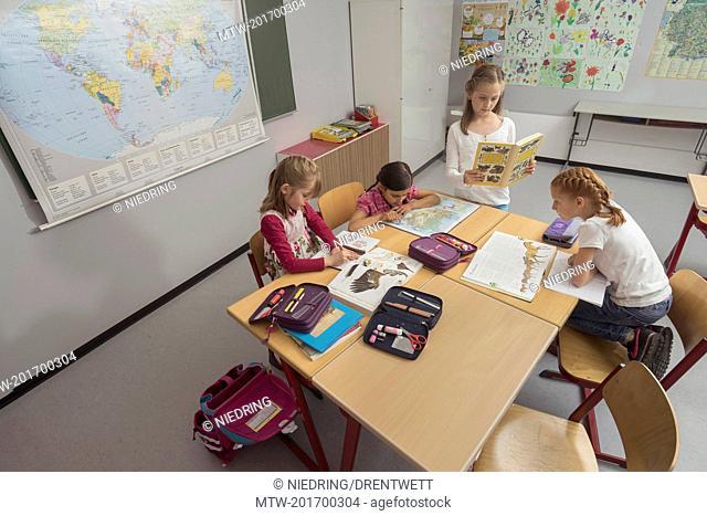 School children reading books in classroom, Munich, Bavaria, Germany