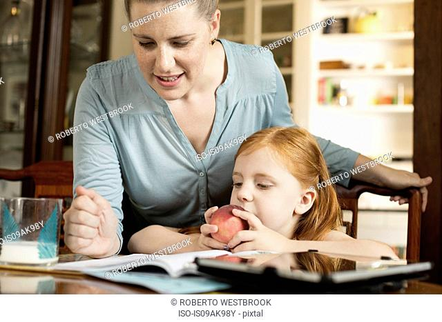 Mid adult mother helping daughter with homework at dining room table