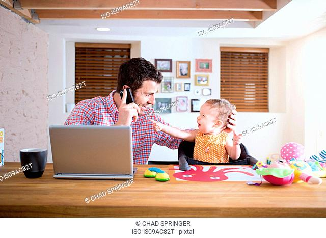 Man and baby sitting at kitchen counter making phone call