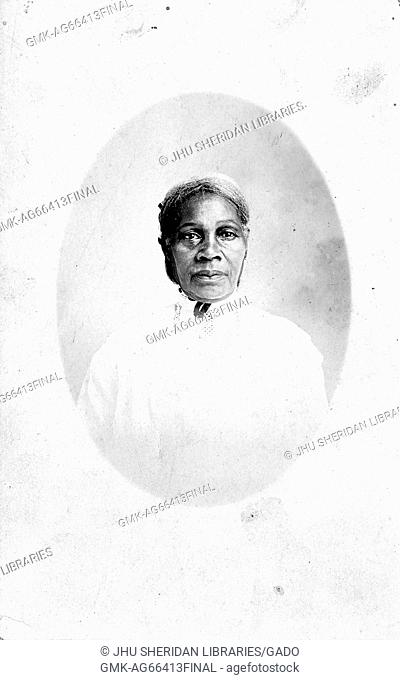 Oval half length portrait of mature African American woman wearing a white dress, with a serious facial expression, 1944
