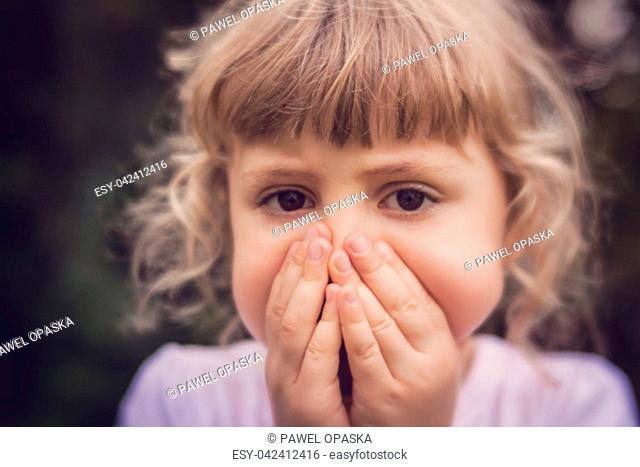 Little girl standing in the park with her hands covering her mouth indicating she is scared or worried