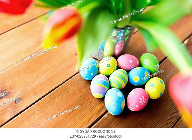 easter, holidays, tradition and object concept - close up of colored easter eggs and tulip flowers in bucket on wooden table