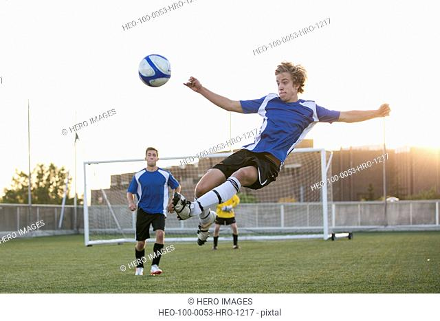 Soccer player in mid-air kicking ball