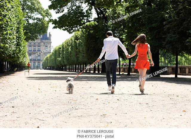 Couple running in a garden with a puppy, Terrasse De l'Orangerie, Jardin des Tuileries, Paris, Ile-de-France, France