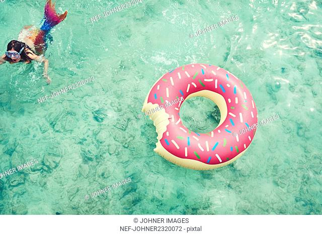 Girl swimming by inflatable ring