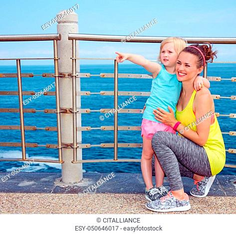 Look Good, Feel great! Happy mother and child in fitness outfit on embankment pointing on something