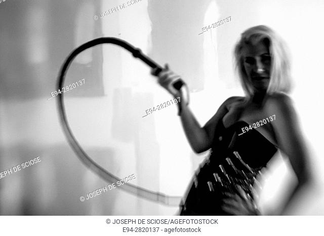 52 year old blond woman wearing a corsett and swinging a whip, black and white