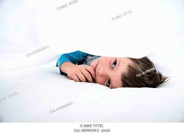 Boy lying between white bed sheets