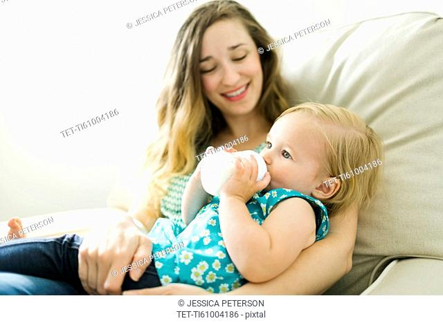 Mother feeding baby girl (12-17 months) in living room