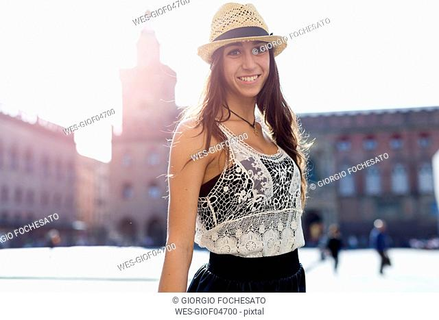 Italy, Bologna, portrait of fashionable young woman wearing straw hat at backlight