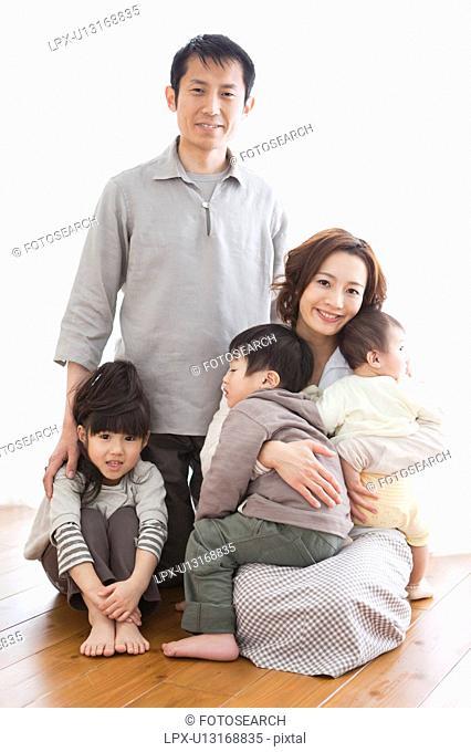Portrait of family sitting on hardwood floor
