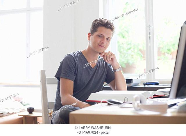 Portrait of handsome young male university student studying at home