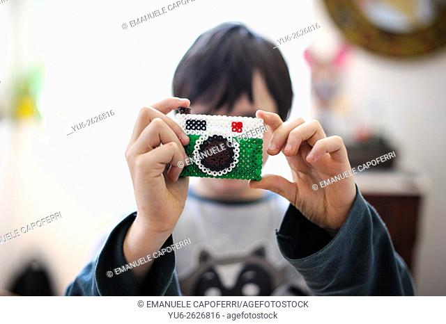 Child plays with camera built with beads