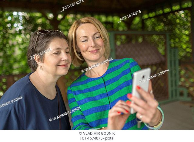 Smiling woman taking selfie with mother at gazebo