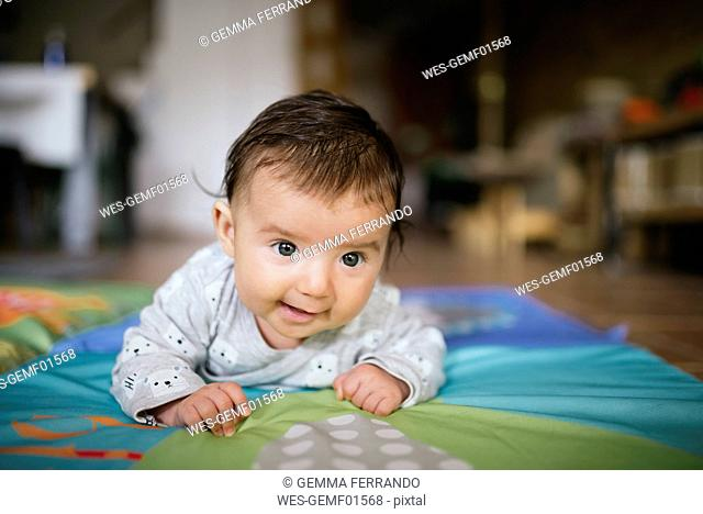 Baby girl crawling on blanket at home