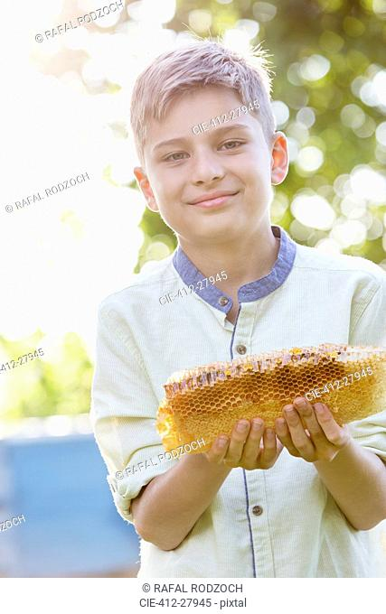Portrait confident boy holding fresh honeycomb