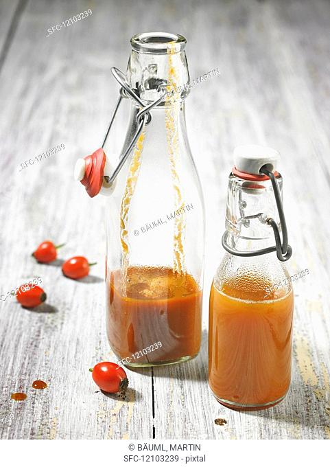 Rose hip juice in two partially filled clip top bottles