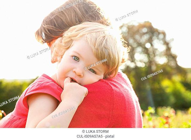 Portrait of toddler daughter resting on mothers shoulder in flower field