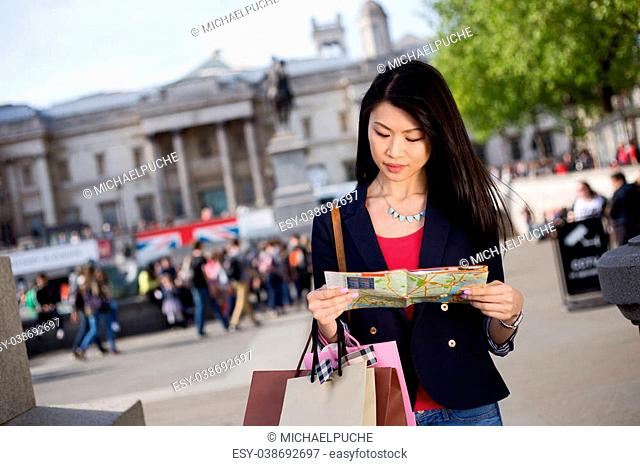 young chinese tourist reading a map