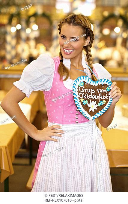 Young woman holding Gingerbread heart at Oktoberfest, Munich, Germany