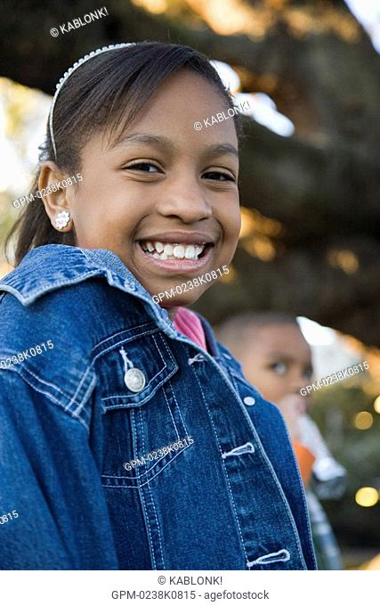 Portrait of happy African American girl outdoors, looking at camera