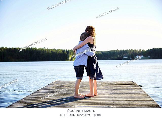 Children hugging on pier